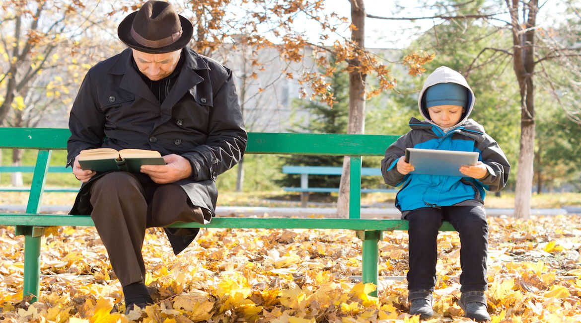 Elderly man reading his book and a small boy looking at his tablet computer sit ignoring each other at either end sharing a park bench on a cold autumn day